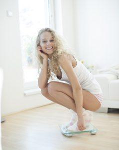 una mujer esbelta y satisfecha de pie sobre el peso
