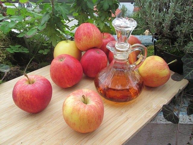Manzanas frescas y una botella de vinagre de sidra de manzana sobre la mesa