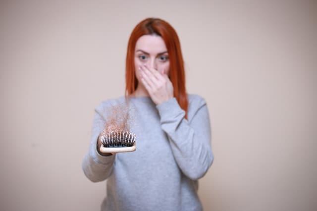 una mujer mira un cepillo completo de cabello