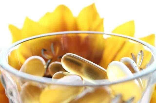 tabletas en un vaso, flor amarilla en el fondo