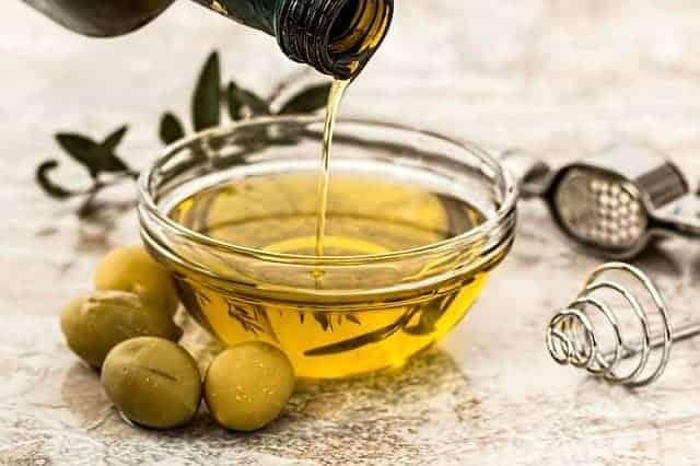 aceite vertido en un bol, con aceitunas verdes al lado