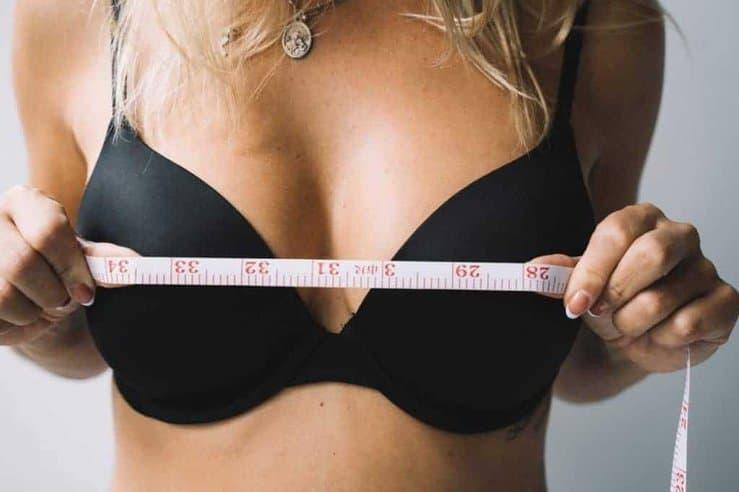 una mujer mide sus senos con un centímetro