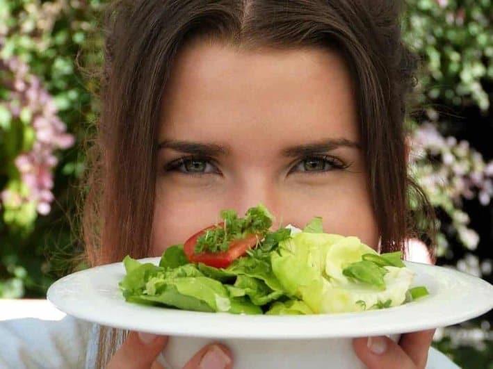la mujer sostiene un plato de ensalada