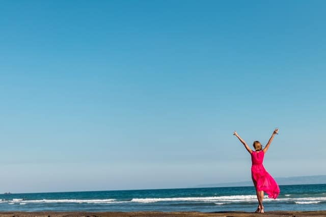 mujer en vestido rojo de pie en la costa